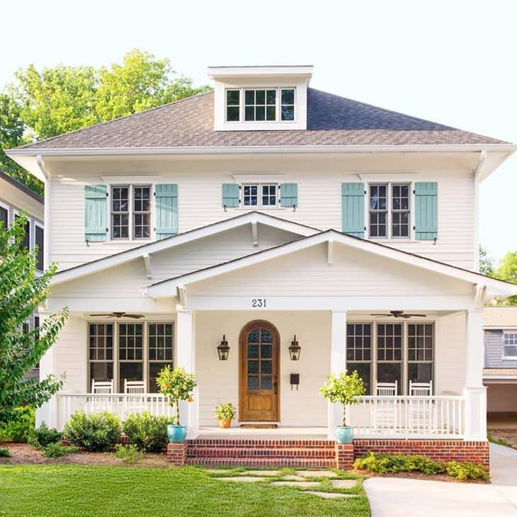 Farmhouse exterior with teal shutters and arched front door