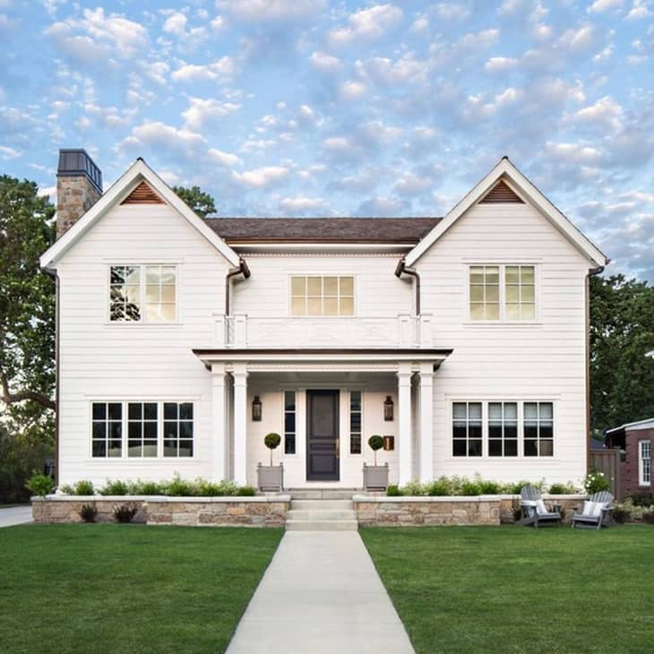Traditional white farmhouse exterior with black front door