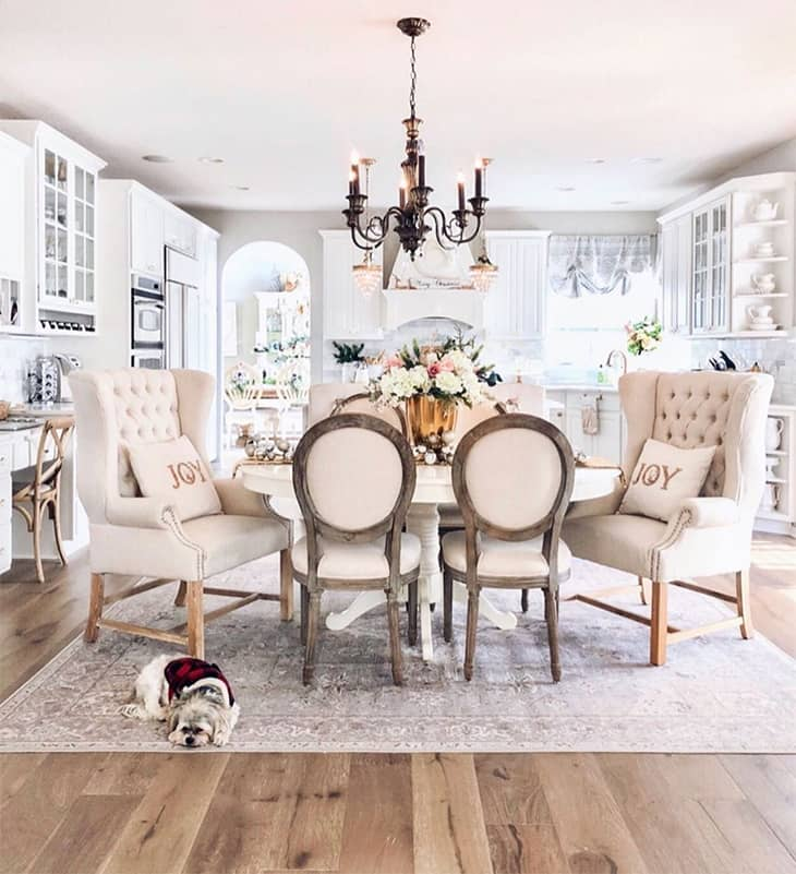 farmhouse dining room with white desk and upholstered dining chairs, black chandelier and big area rug