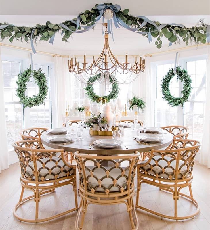 farmhouse dining room with rattan dining chairs and round table and big chandelier