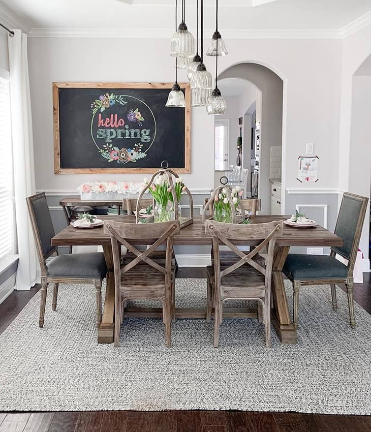 modern farmhouse dining room with big wood table and six dining chairs and table decor