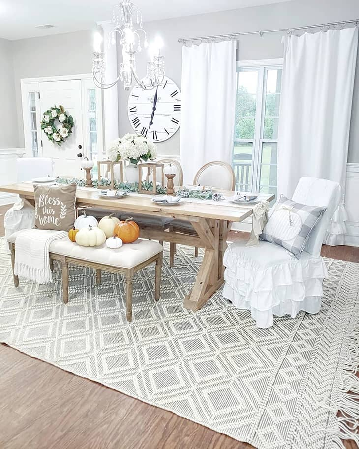 white farmhouse dining room with bench and dining chairs with big area rug