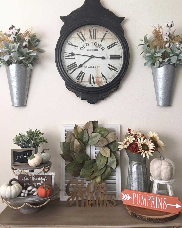 magnolia wreath below rustic clock and metal wall vase
