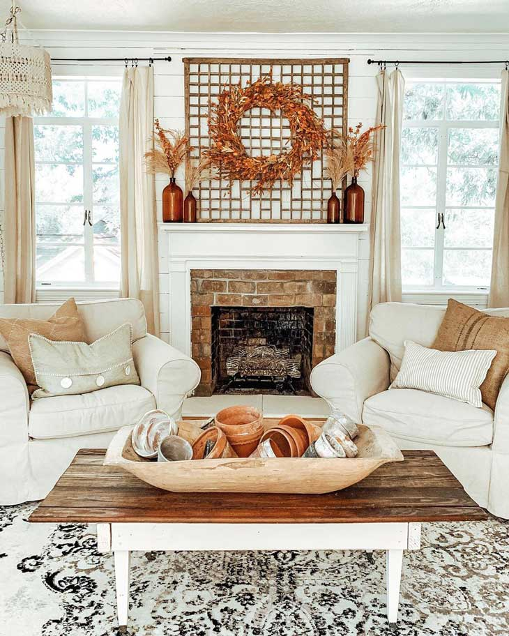 orange fall wreath above brick fireplace in livingroom