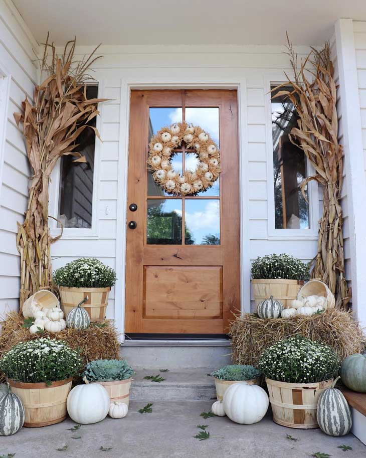 fall front door decor with pumpkin wreath and dried cornstalks