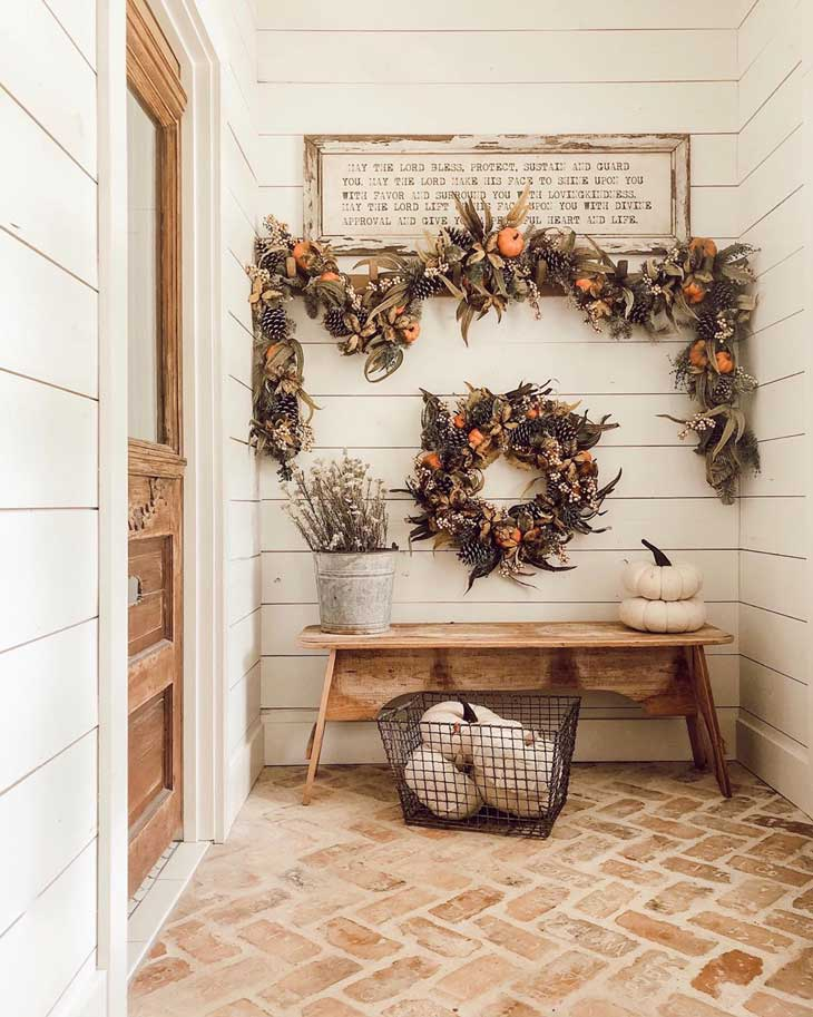 mini pumpkins and pines wreath below fall garland in an entryway