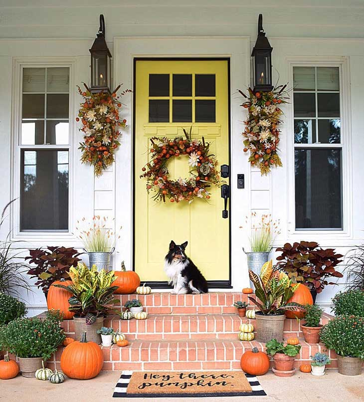 Fall wreath on a yellow front door with pumpkin decor