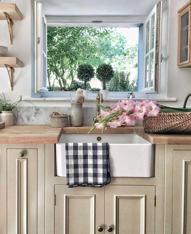 farmhouse sink with buffalo check towel, butcher block and cooper faucet