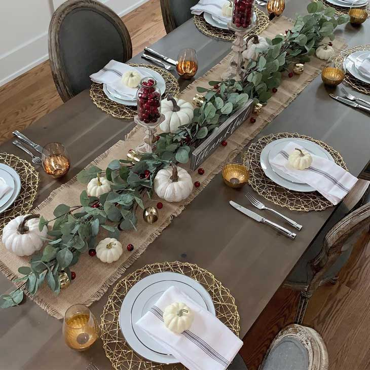 thanksgiving table with green garland and pumpkins