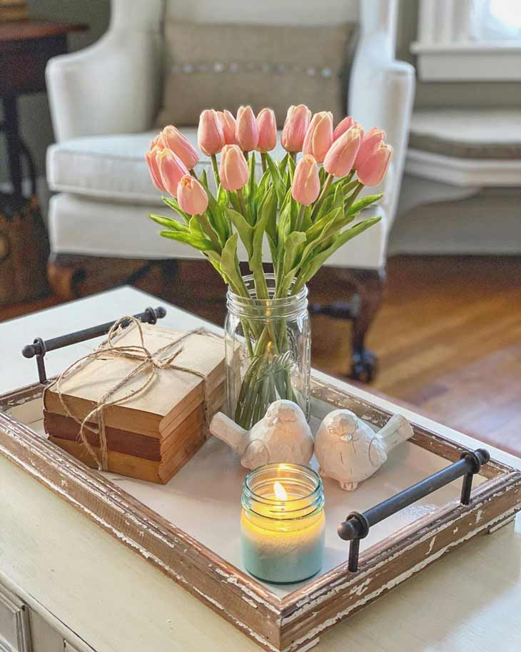 coffee table centerpiece with serving tray with metal handles, fresh tulips and decorative books