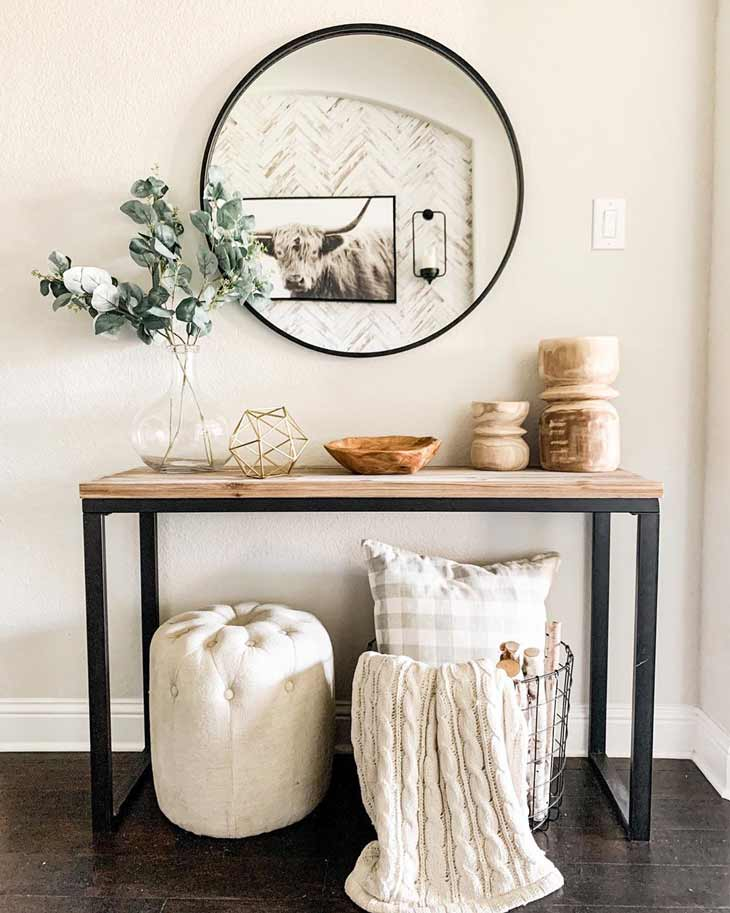 Entryway table with metal legs, neutral decor and round mirror