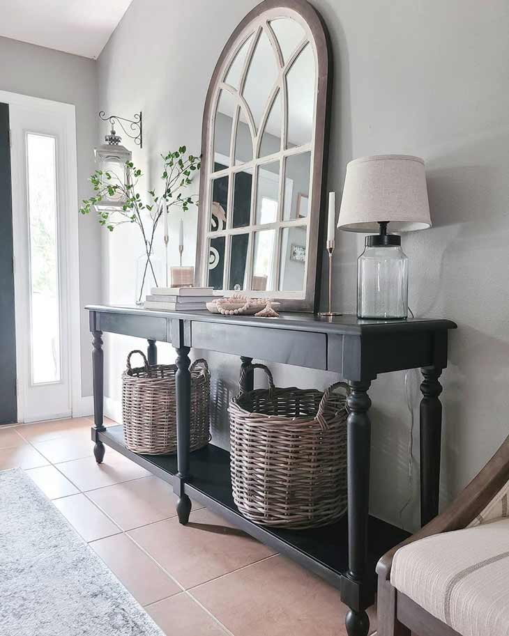 black entryway table decor with arched mirror and baskets
