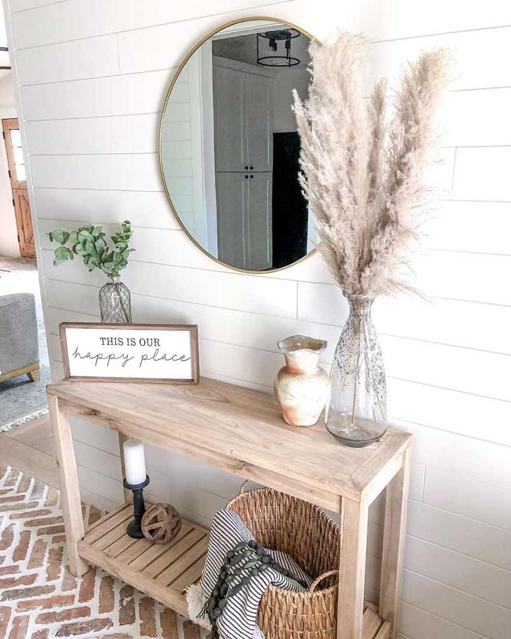 Small entryway table in neutral tone with pampas decor and round mirror above