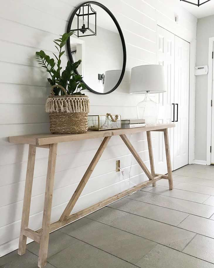 reclaimed wood entryway table with basket and lamp decor and round mirror above it. Slender entry table