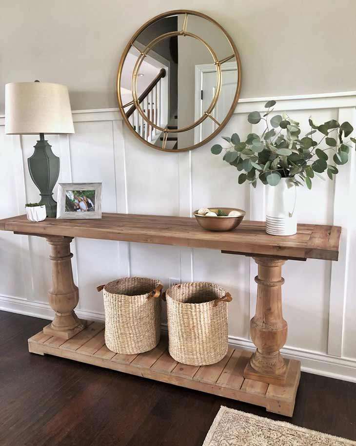 modern farmhouse entryway table with two legs decorated with baskets, flower arrangement and round mirror above on a panelled wall