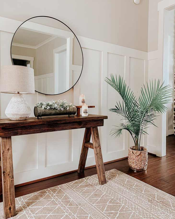 dark wood entryway table with flower decor, table lamp and round mirror