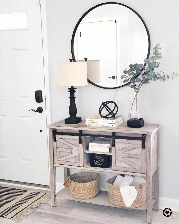farmhouse style entryway table with black decor accents and round mirror above it