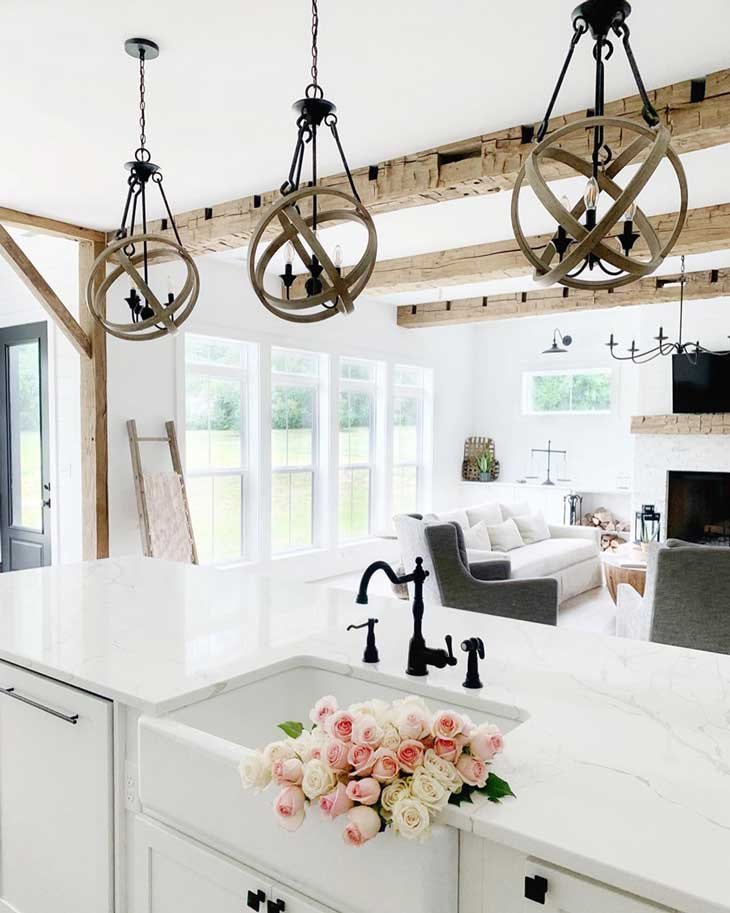 round wood pendant lighting over white kitchen countertop with farmhouse sink in kitchen island and black faucet