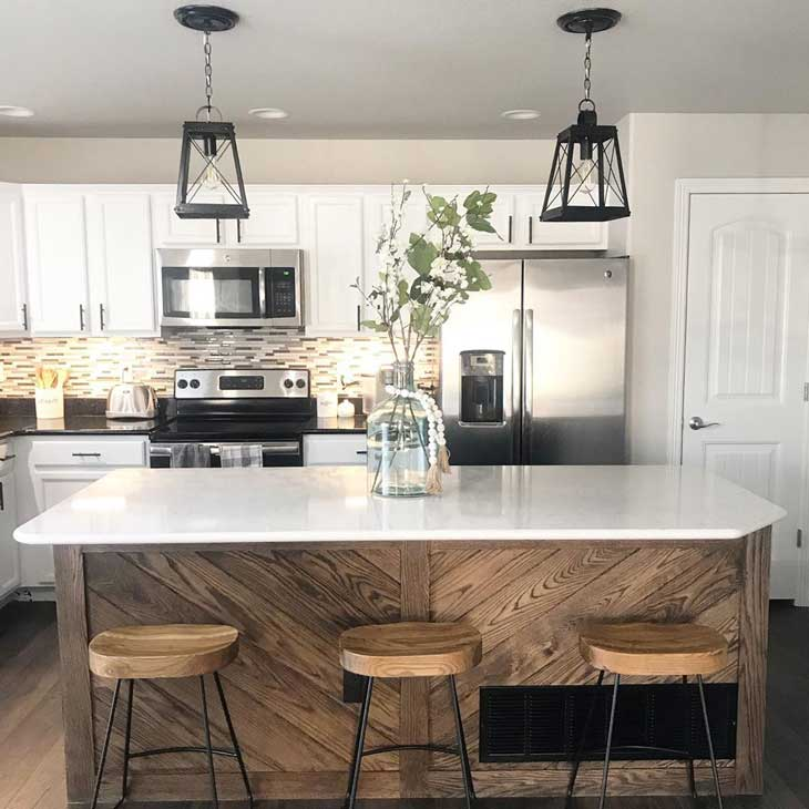 black lantern island lighting over wood kitchen island with white countertop and island centerpiece