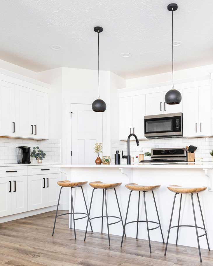 black metal pendant lights over white kitchen island in a white kitchen with black hardware