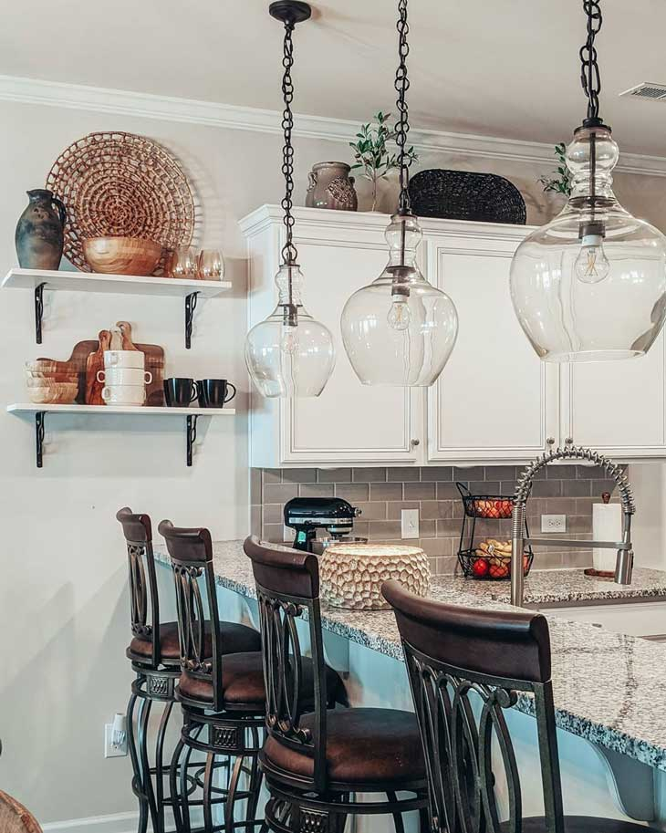 glass pendant lighting over kitchen bar with open shelving