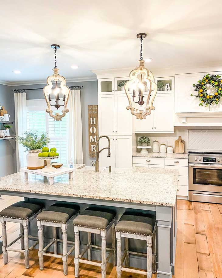 Wood Country-Cottage Chandeliers over grey kitchen island with marble counter top and upholstered bar stools