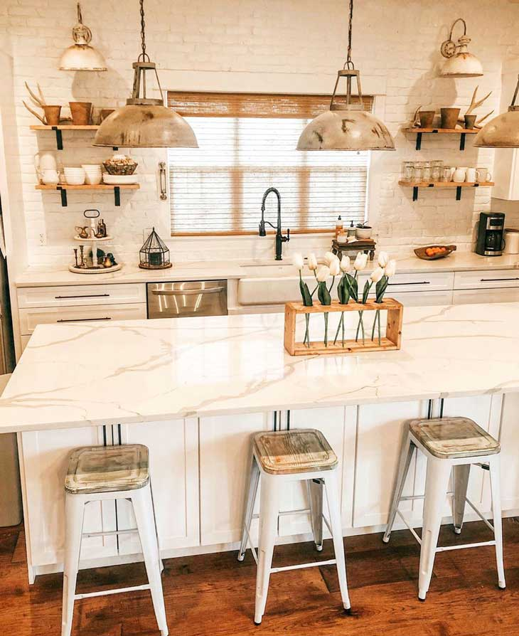 barn-style pendants over white kitchen island with white marble countertop and metal barstools