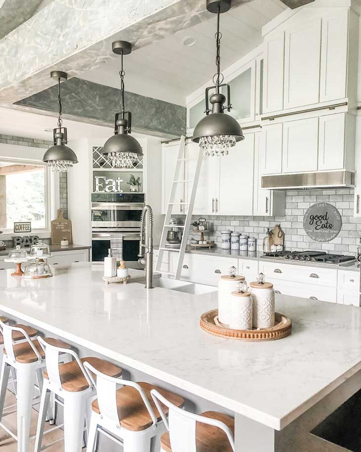 Black industrial pendants over white kitchen island with white marble countertop