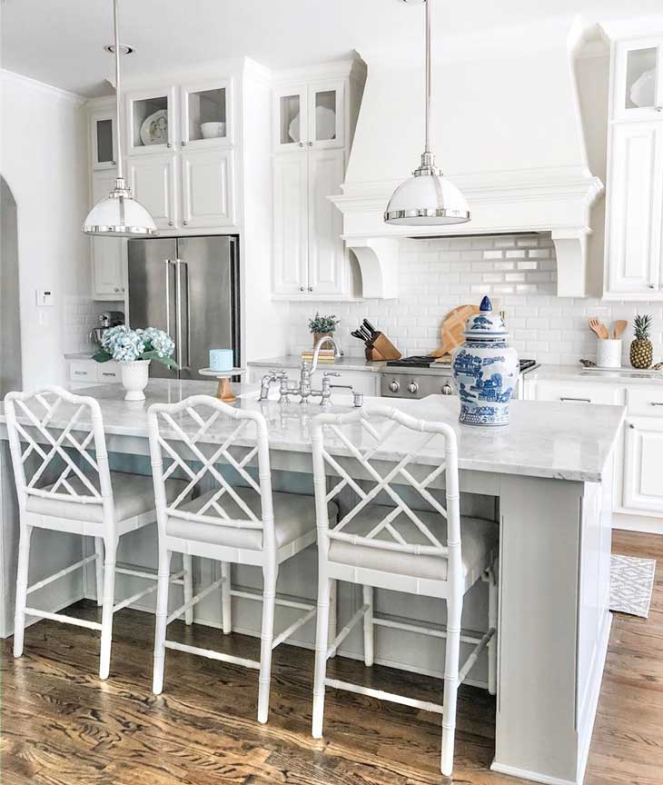pendant lighting over light grey kitchen island with white bar stools