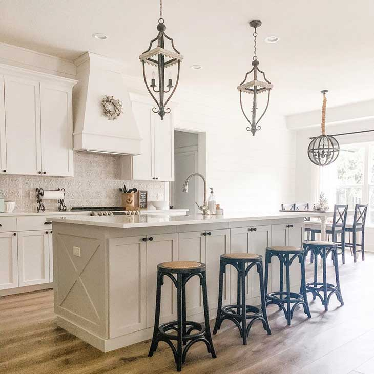 rustic pendant lights over big kitchen island with black barstools