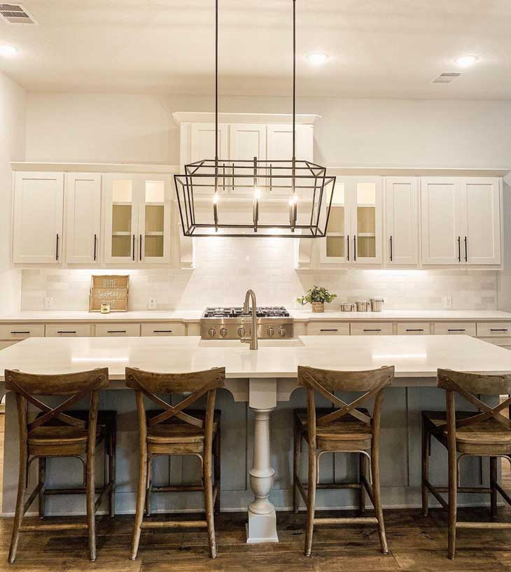 open frame lantern chandelier over kitchen island with white countertop and wood barstools in a white kitchen