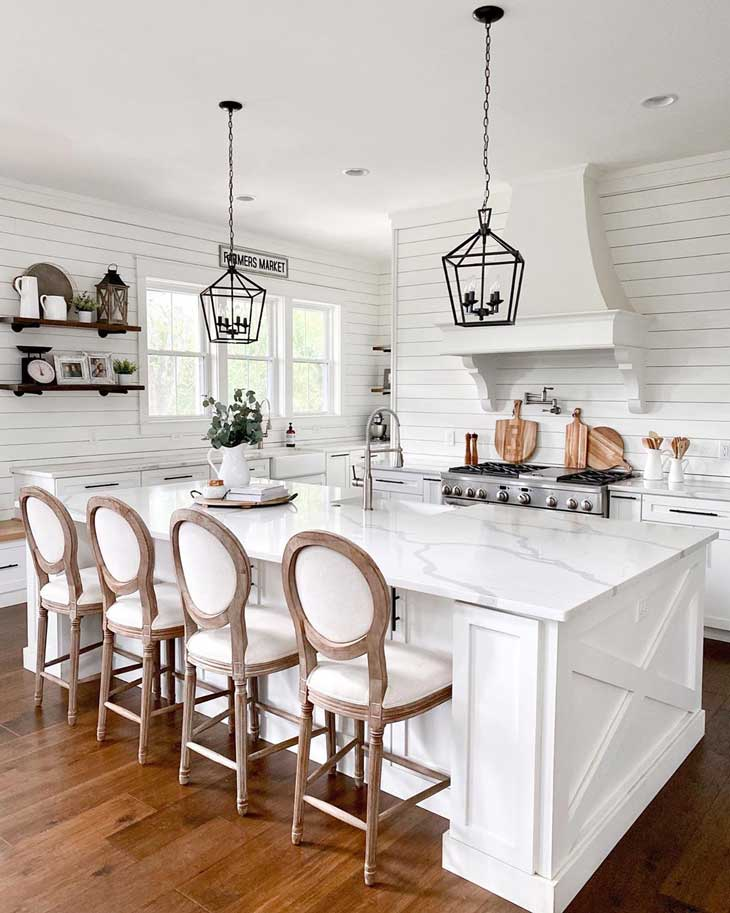black pendant lights over white kitchen island with marble countertop and wood upholstered barstools in a kitchen with shiplap backsplash