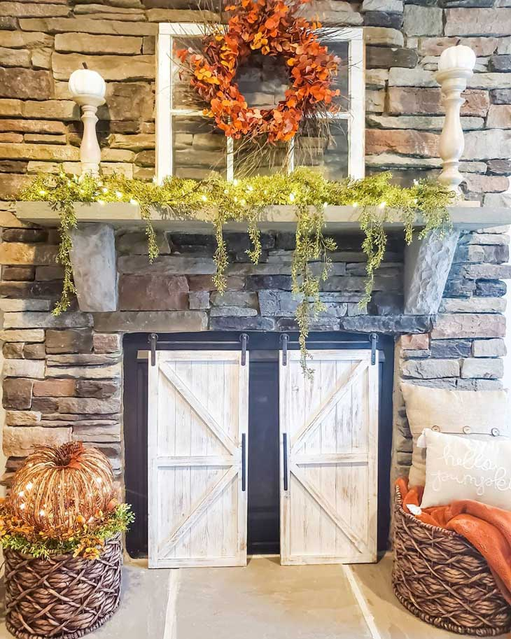 Stone fireplace with fall decor and orange wreath