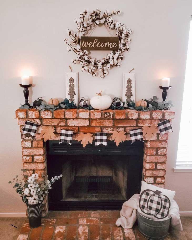 Fall fireplace decor with buffalo check and white pumkins