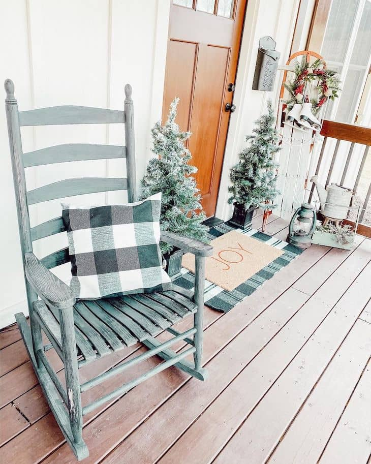 Christmas front porch with small Christmas trees, buffalo check, vintage sled and ice skates.