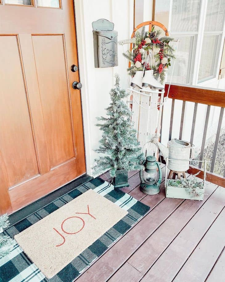 Christmas front door with plaid mat, mini Christmas tree, and antique sled with ice skates