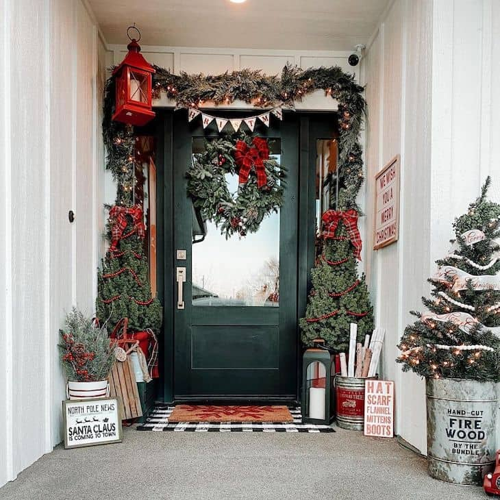 Front porch Christmas decor with cedar garland two trees with red beads and big wreath with red ribbon