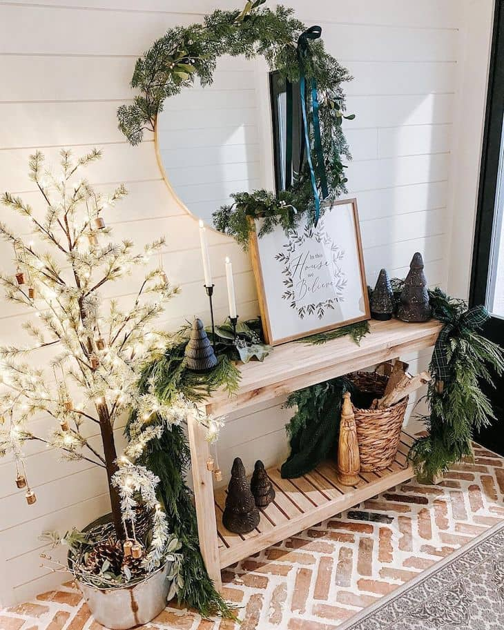 Entry table Christmas decor with big garland, lit tree and round mirror
