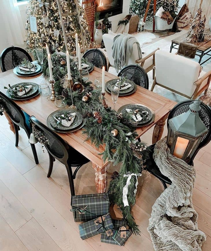 Dining table Christmas decor with big garland and candles. Green and gold Christmas table decor