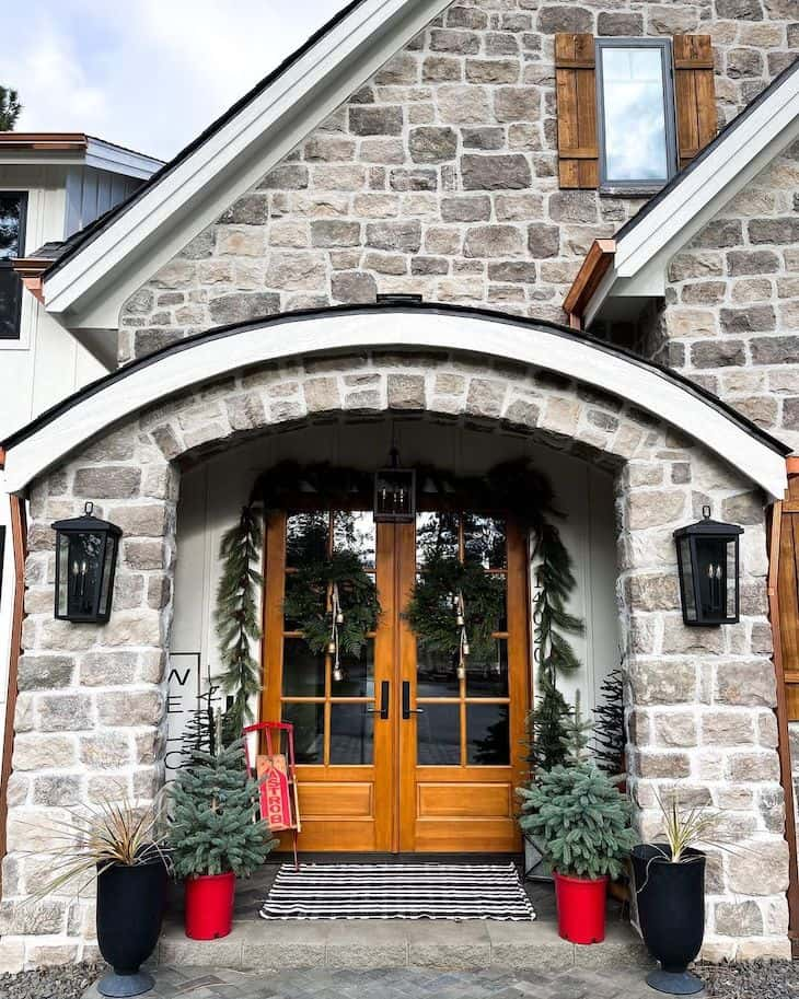 Modern farmhouse Christmas porch with double french door decorated with garland and two wreaths