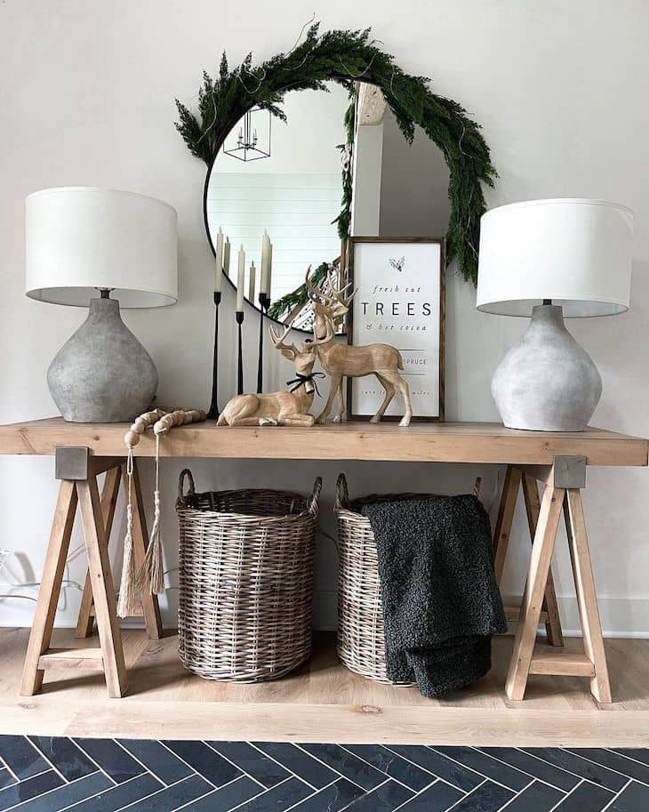 Entryway table with Christmas decor, two table lamps and a round mirror