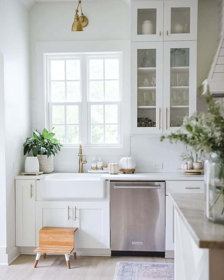 Farmhouse kitchen sink with gold faucet and window above it