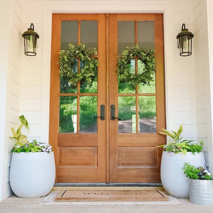 double french front door in wood finish with two wreaths