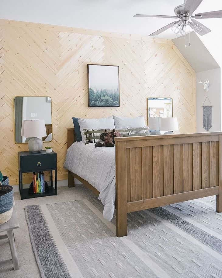 Boys kids room with wood bed, herringbone shiplap wall and black cabinet