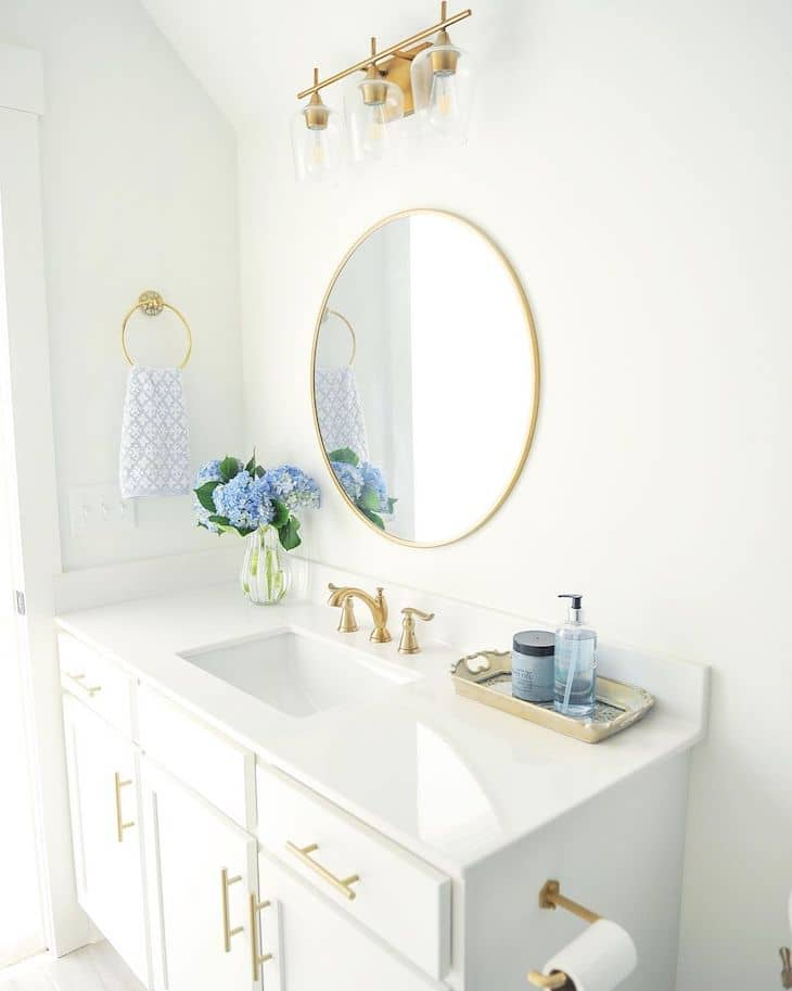 Guest bathroom vanity with one sink and round mirror