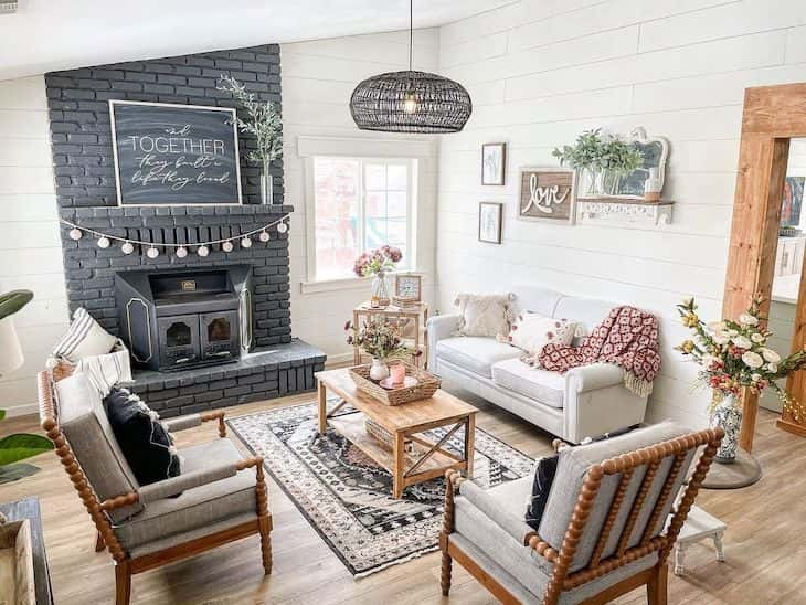 Farmhouse living room with black brick fireplace and shiplap walls in White Dove color