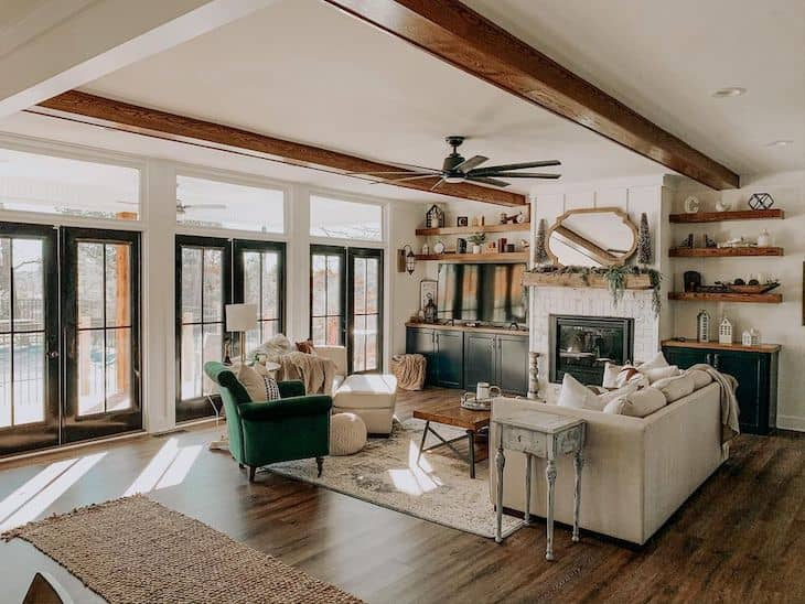 farmhouse living room with wood beams, black french doors, dark hardwood flors and built ins