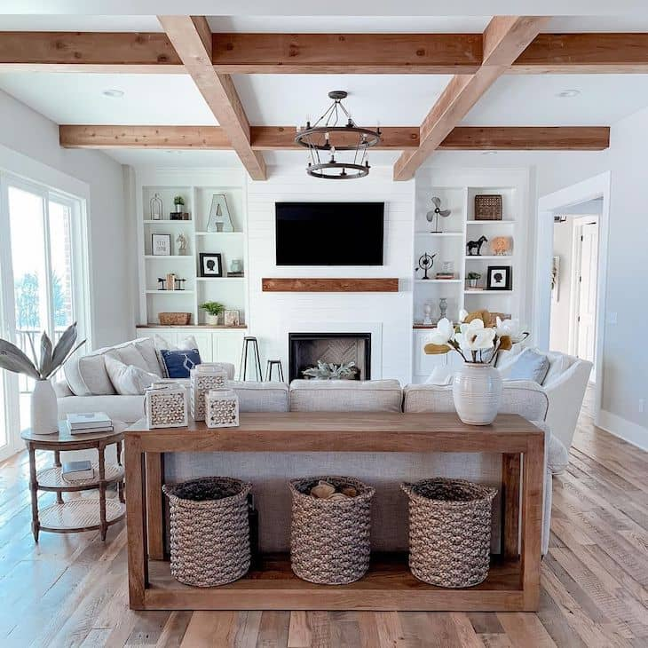 modern farmhouse living room with wood beams, shiplap fireplace, linen couches and wood sofa table