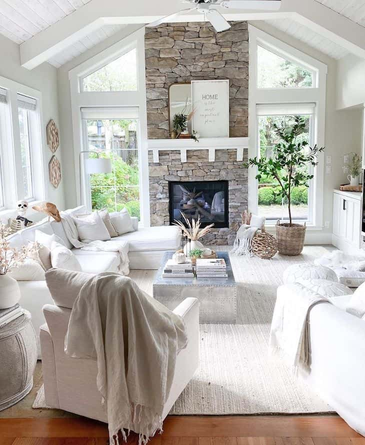 Open concept living room with white beams, stone fireplace, white sectional and windows on each side of fireplace