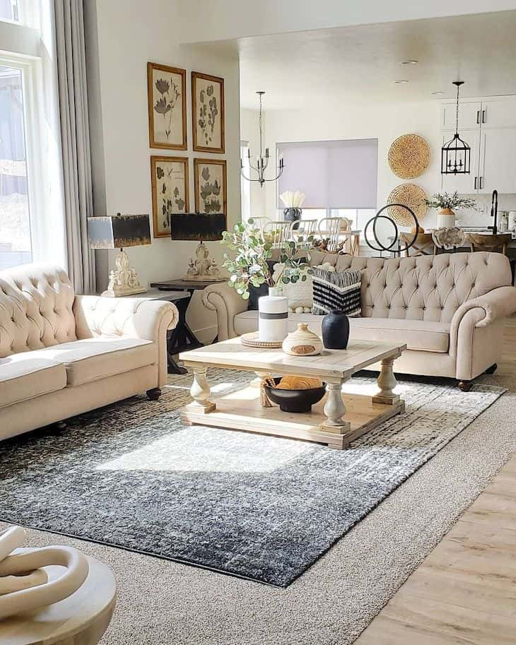Classic farmhouse living room in neutral tones with chesterfield sofas and wood square coffee table